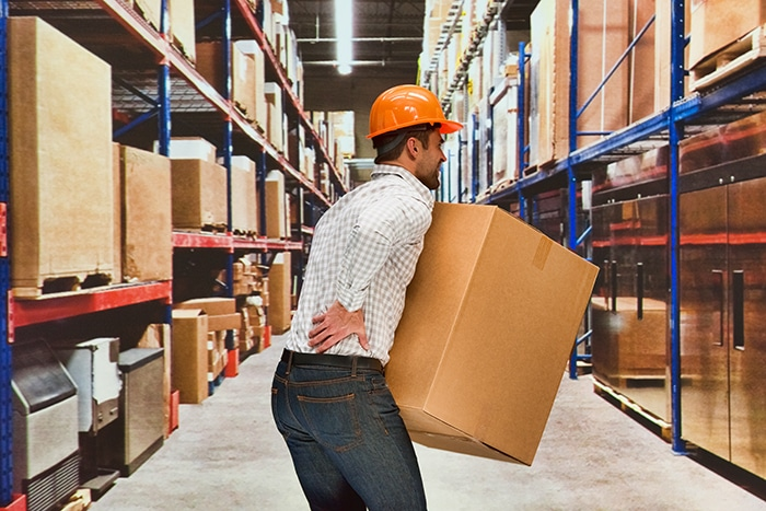 Worker feeling back pain in warehouse