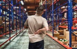 Employee having back pain in warehouse